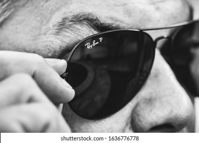 Ray-ban glasses, black and white photo. Man wearing ray-ban glasses and touching it with his hand. Brasilia, Federal District - Brazil. February, 05, 2020.