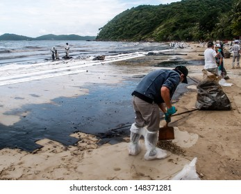 RAYONG -JUL 31: People clearing contaminated sand at the Aou Prow beach, Rayong, Thailand on Jul 31, 2013. The spilled oil came from the accidental leaking during oil tanker transferring on July 27.