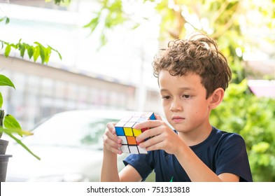 Rayong Province, Thailand - November 7th, 2017:  Cute boy plaiyng with the Rubik's Cube. Rubik's cube invented by a Hungarian architect Erno Rubik in 1974.
