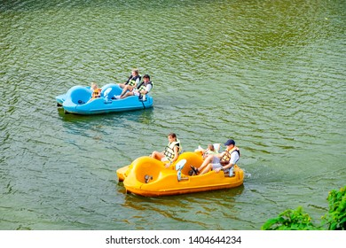 Rayong, Thailand - 19 May 2019 : Tourists anjoy to play pedal boat in the lake park at Brookside Valley hotel and resort