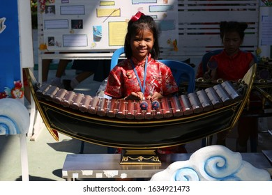 Rayong, Thailand - 22nd January, 2020: A young primary school girl plays the ranat ek, a traditional Thai percussion instrument similar to a xylophone, at a school in eastern Thailand.