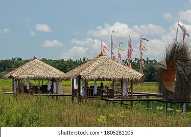 Rayong, Thailand - 29th August, 2020: Small thatched wooden huts surrounded by nature and used as individual dining rooms at a rural restaurant called Somtam Sadit in Ban Kai district, Rayong.