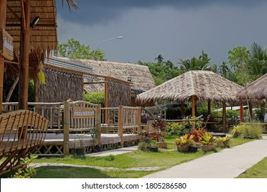 """Rayong, Thailand - 29th August, 2020: Path and garden among small thatched wooden huts used as dining areas at rural restaurant Somtam Sadit, Ban Kai district. Thai sign is the name """"Aunt Gold Deer""""."""