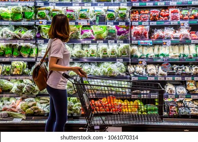 Rayong , Thailand - April 1 , 2018 : A woman is looking for organic vegetable in the shelf at TOP supermarket. Local fresh vegetable is good for healthy people