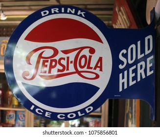 """Rayong, Thailand - April 24th, 2018: A vintage round metal store-front marketing sign for the Pepsi Cola brand with the message """"Pepsi Cola Sold Here""""."""