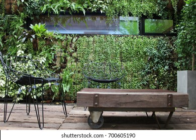 Rayong, Thailand - August 20th, 2017: The wooden terrace for outdoor seating of Ookull Cafe Rayong backs onto the building exterior, a vertical garden of green tropical plants, Ban Laeng, Rayong.