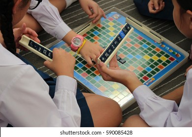 RAYONG, THAILAND - CIRCA DECEMBER 2016: A group of girl primary school students learn maths informally by playing a number Scrabble style board game.