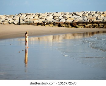 Rayong, Thailand - February 17th, 2019: A young woman using a mobile phone stands at the edge of the ocean at Saeng Chan beach, a popular tourist destination in the coastal city of Rayong.