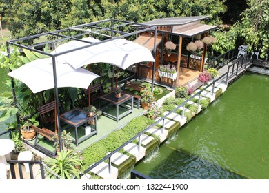 Rayong, Thailand - February 24th, 2019: Outdoor seating overlooking a pond at a newly built cafe surrounded by nature in the rural district of Khao Yai Da in Rayong, eastern Thailand.
