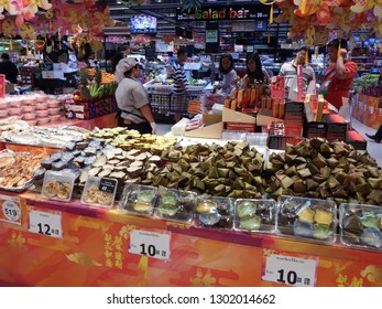 Rayong, Thailand - February 2nd, 2019: A staff member serves customers at a supermaket on a stall filled with food products for celebrating the Spring Festival and the Chinese Lunar New Year.