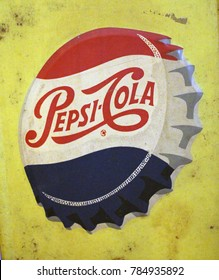 Rayong, Thailand - January 2nd, 2018: A vintage advertising sign board for the Pepsi Cola brand featuring a bottle top illustration on yellow background.