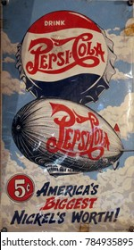 Rayong, Thailand - January 2nd, 2018: A vintage advertising signn board for the Pepsi Cola brand featuring a bottle top and Zeppelin air balloon illustration.