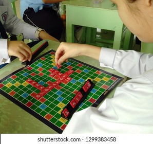 Rayong, Thailand - January 4th, 2019: High school school students play a mathematics version of the famous Scrabble board game popular in Asia where players must create sums as opposed to words.