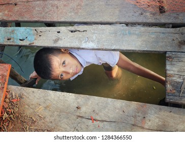 Rayong, Thailand - January CIRCA, 2019: See through under wooden bridge hole. There are many young kids in Thailand country side looking for food, shortage and starving. They work hard job for food.