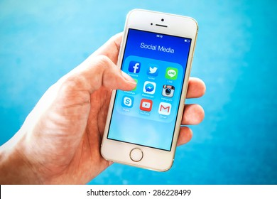 RAYONG, THAILAND - June 03 , 2015: All of popular social media icons on smartphone device screen with hand holding on Apple iPhone 5s.