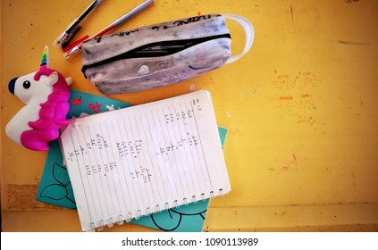 Rayong, Thailand - March 21st, 2018: Above view of a real primary student's desk in a classroom with math sums working out in a notebook, unicorn toy and a pencil case.