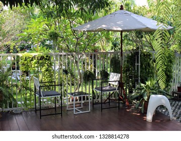 Rayong, Thailand - March 3rd, 2019: A garden terrace at a local cafe decorated with tables and chairs and a sun umbrella overlooking a green tropical garden, Rayong city, eastern Thailand.