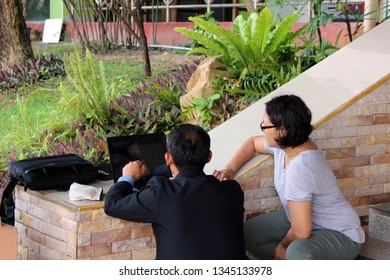 Rayong Thailand - March 9th, 2019: A male and a female member of staff crouch down by steps overlooking a garden to use the wall to work on a laptop computer together.