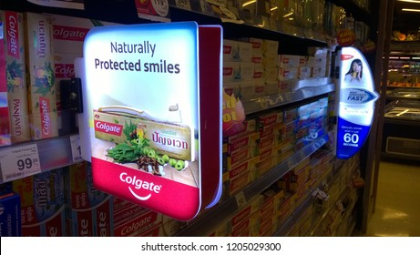 Rayong, Thailand - October 16th, 2018: Illuminated in store shelf advertising sign in a supermarket aisle for Colgate, a multi-national manufacturer of oral hygiene products.