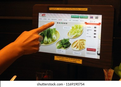 Rayong, Thailand - September 1st, 2018: A customer orders food by using a digital touchscreen menu at their table inside an MK restaurant. MK Restaurants is the most popular suki chain in Thailand.