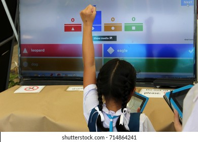 """Rayong, Thailand - September 7th, 2017: A Thai primary school girl celebrates her correct answer during a game of """"Kahoot!"""", an online game based learning platform used as educational technology."""