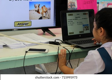 Rayong, Thailand - September 7th, 2017: A Thai primary school girl studies English language through technology by playing a game on a laptop connected to a TV, Rayong, eastern Thailand.