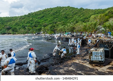 RAYONG,THAILAND-July 31 : Plenty of people are trying to remove the crude oil on oil spill accident by PTT on Ao Prao Beach at Samet island on July 31,2013 in Rayong,Thailand