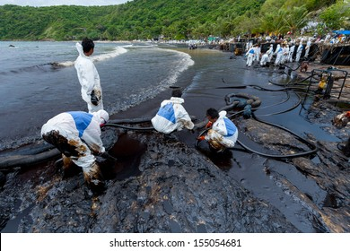 RAYONG,THAILAND-July 31:Workers use the high pressure suction suck the crude oil and plenty of people helping on oil spill accident on Ao Prao Beach at Samet island on July 31,2013 in Rayong,Thailand