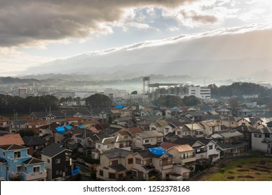 Rays of early morning sun shine through break in the clouds on Japanese neighborhood damaged by typhoon