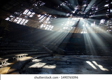 Rays of life through the decaying roof of the abandoned soviet building