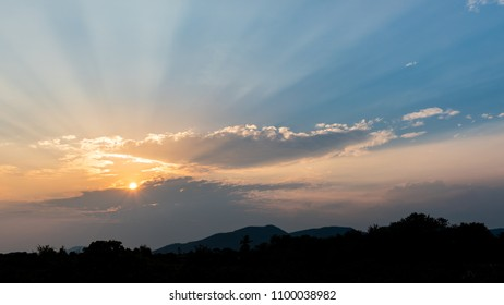 Rays of light shining through the clouds over mountains