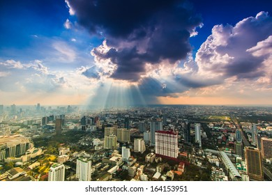 Rays of light shining through dark clouds city Bangkok, Thailand