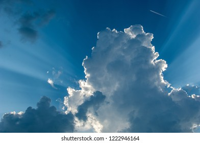 Rays of light shining through fluffy clouds.