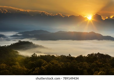 Rays of light of the sun rise in the morning over the mountain range