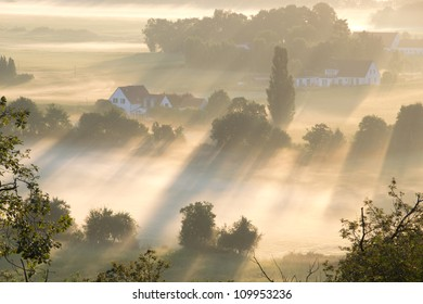 Rays of morning light illuminate fields and houses in the Netherlands on a foggy morning.