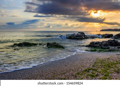 rays of the morning sun behind the clouds illuminate sea and coastal sandy beach with small rocks