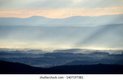 Rays of morning sun streaming through thick fog and mist into a valley nestled between layered multicolored mountain ridges and a peach and blue colored sky in the Appalachian Mountains