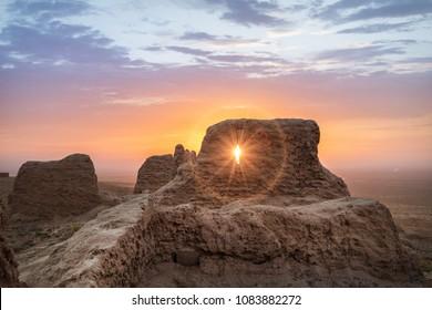 Rays of rising sun permeate through ruins of ancient Ayaz Kala fortress in Kyzylkum desert, Uzbekistan