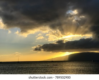 Rays of the setting sun shoot from behind a dark gray cloud hanging above the island of Lanai in this sunset and island view across the ocean from Lahaina, Maui.