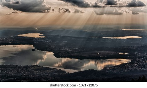 rays of sun in the clouds above the lakes of the province of Varese in winter season