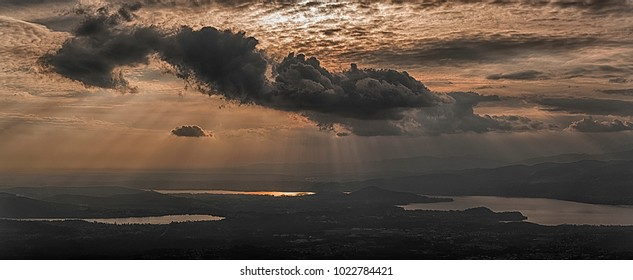 rays of sun in the clouds above the lakes of the province of Varese in winter season seen from the mountain path