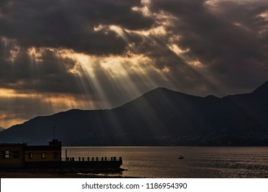 Rays of Sun through the clouds on the lake at the end of the autumn day