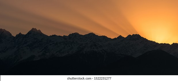 Rays of sunlight in the sky behind the Panchachuli mountains in Munsyari during sunrise.