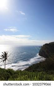 Rays of sunlight streaming down on a view of Kohala Mountains meeting the Pacific Ocean at Pololu Valley, Kohala Coast, Hawaii, USA
