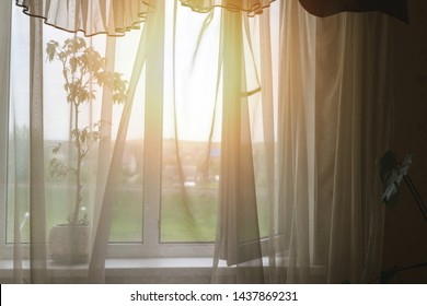rays of sunlight through transparent curtain of open window of room shine with soft light into bedroom from street, light fresh wind blows decorative curtain on window