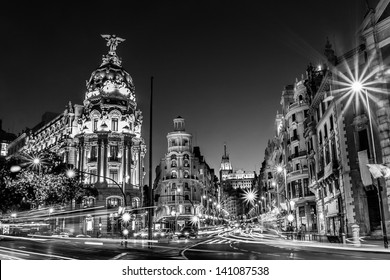 Rays of traffic lights on Gran via street, main shopping street in Madrid at night. Spain, Europe. Black and white photo.