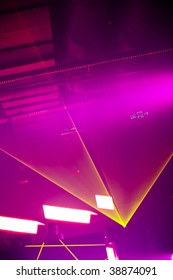rays of yellow laser light on pink background at disco club