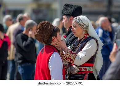 "RAZLOG, BULGARIA - APRIL 13, 2015: Helping with the make-up, during the traditional folklore festival ""1000 national costumes"""