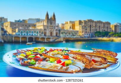 The razor clams with cheese, fresh vegetables and coconut broth on lunch at St Julian's coast with a view on Balluta Bay and Carmelite church, Malta.