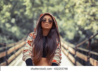 R&B hip hop pop singer. Closeup portrait head shot beautiful pretty teenager brunette young woman  holding skate on woody bridge background. Positive human emotion face expression feeling life concept